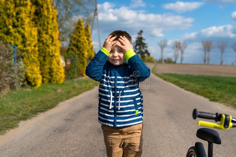 Vijf jaar schattige jongen die op straat staat en zijn hoofd vasthoudt, een kleine fiets zichtbaar en de hemel met wolken royalty-vrije stock foto's