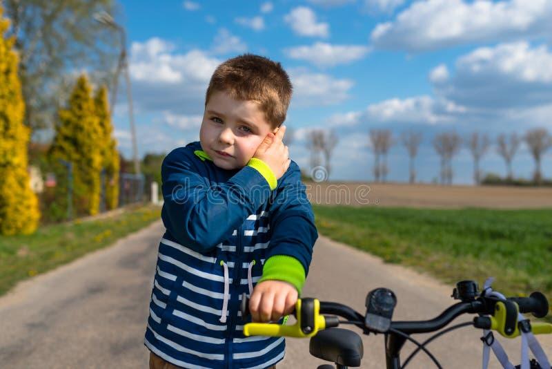Vijf jaar schattige jongen die op straat staat en zijn oor vasthoudt, een kleine fiets zichtbaar en de hemel met wolken stock foto's
