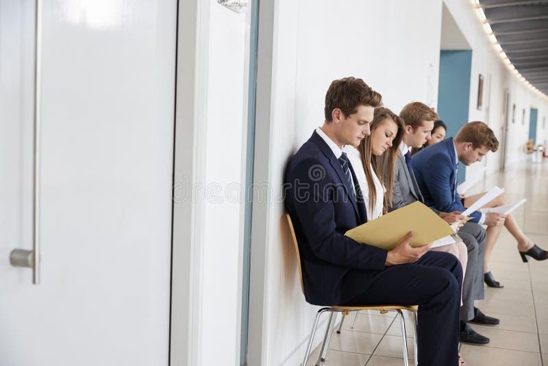 Vijf jonge kandidaten zitten het wachten op baangesprekken stock foto's