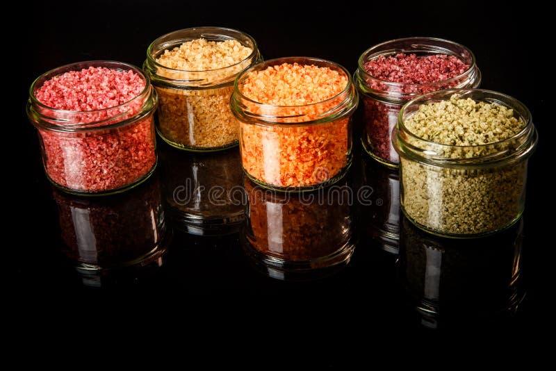 Vijf kleine die glaskruiken met verschillend kleuren overzees zout worden gevuld stock fotografie