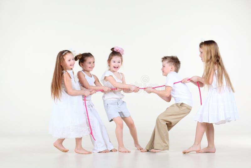 Vijf kleine kinderen trekken over roze kabel. royalty-vrije stock afbeeldingen