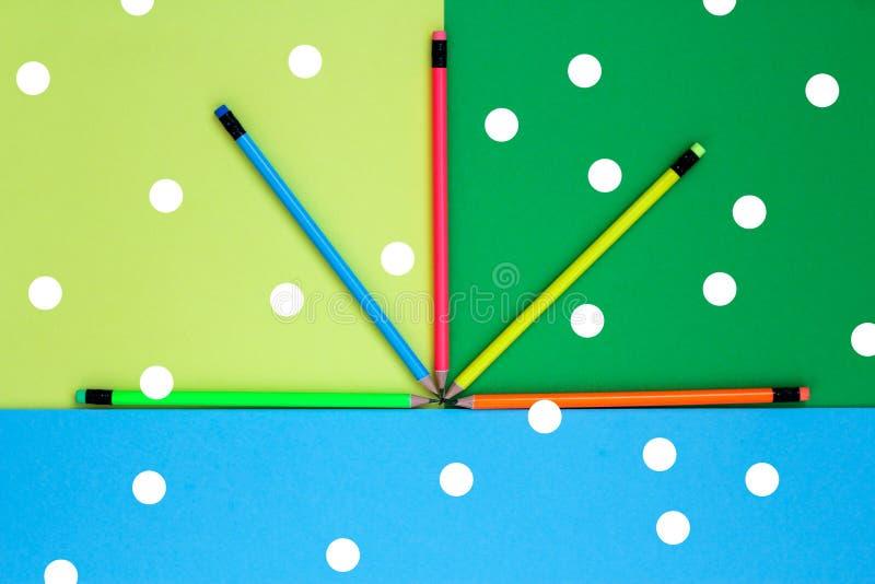 Vijf kleuren van het potlodenneon liggen op een gekleurde achtergrond zoals een ventilator royalty-vrije stock fotografie