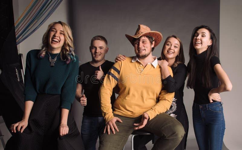 Vijf koele jonge zich en vrienden die verenigen glimlachen De studio schoot in de grijze muur stock foto's