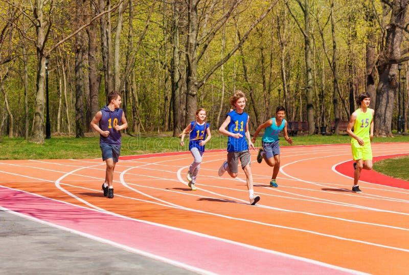 Vijf lopende tieneratleten in het stadion stock fotografie