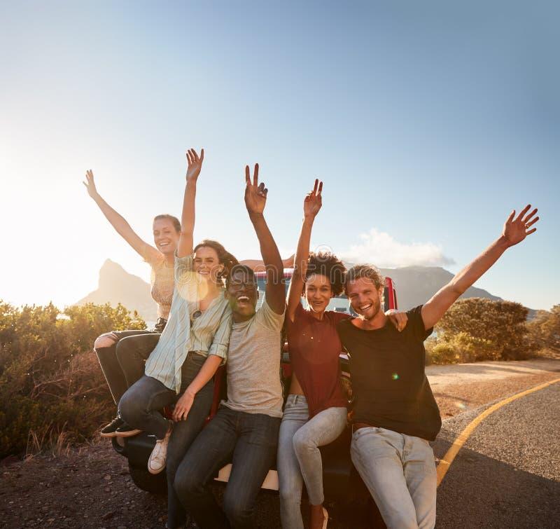 Vijf millennial vrienden op een weg halen het nemen van een onderbreking over, die op de auto die aan camera leunen golven royalty-vrije stock afbeelding