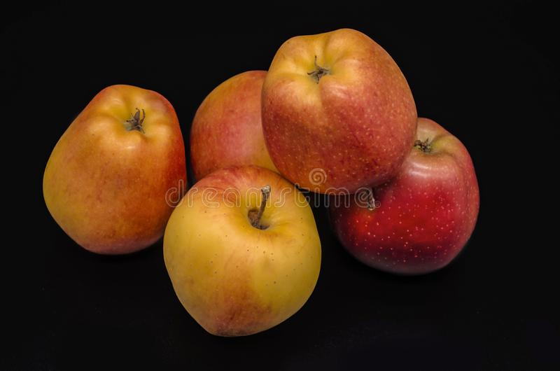 Vijf mooie geel met rode vlekken van rijpe appelen op een zwarte achtergrond royalty-vrije stock foto
