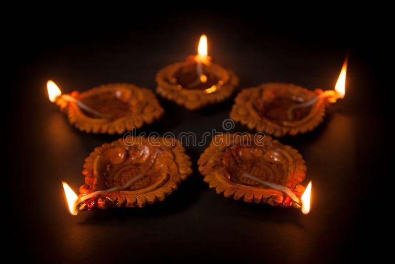 Vijf mooie Met de hand gemaakte Ontwerper Clay Lamps op een rij met het branden van wiek stock foto's
