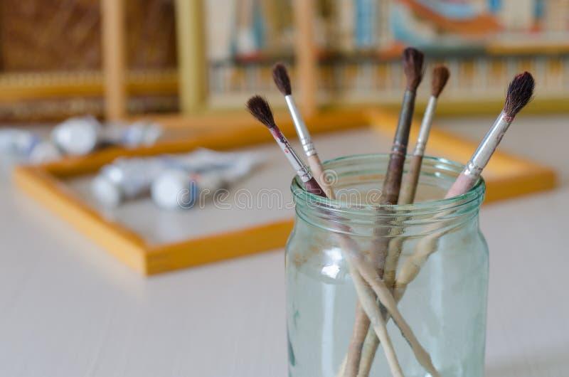 Vijf penselen in een glaskruik Omlijstingen, verf stock foto