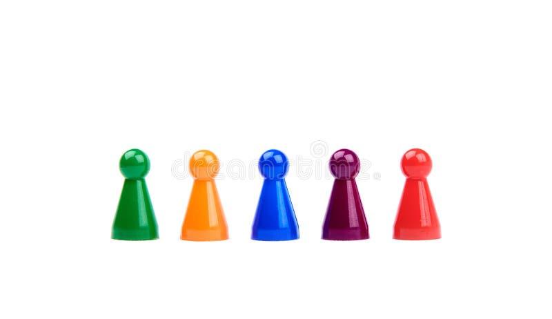 Vijf plastic speelgoed - speelstukken met verschillende kleuren als divers team die zich op een rij die bevinden, op witte achter stock afbeeldingen
