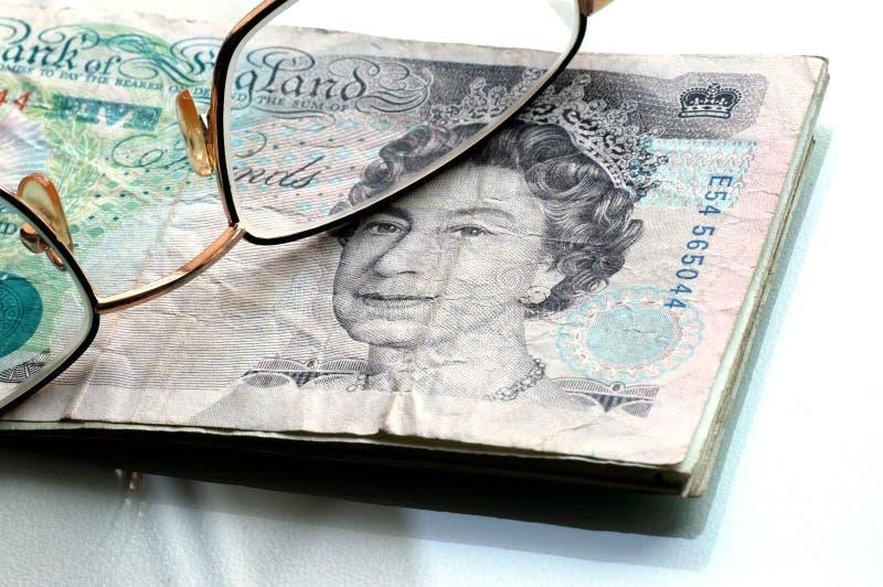 Vijf ponden en glazen royalty-vrije stock afbeelding