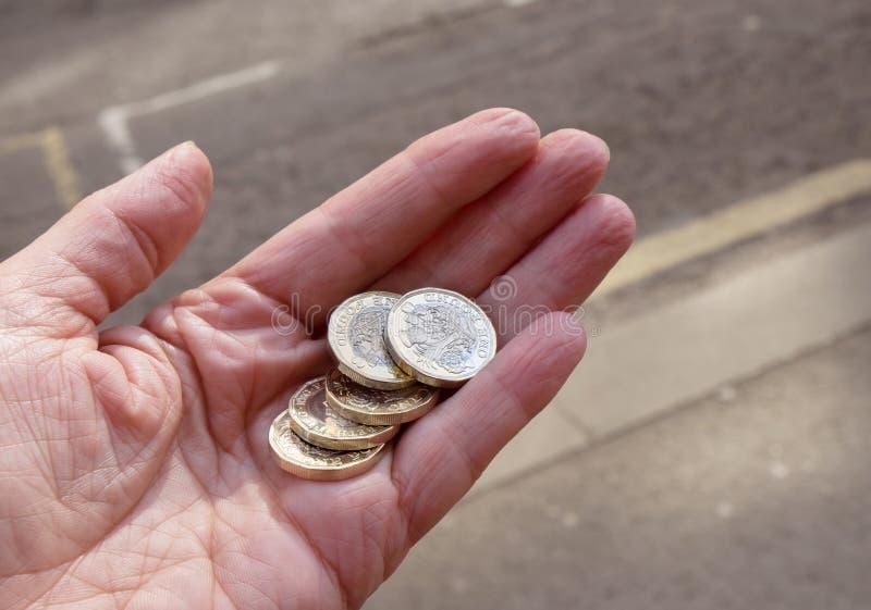 Vijf pondenmuntstukken in een hand stock foto's