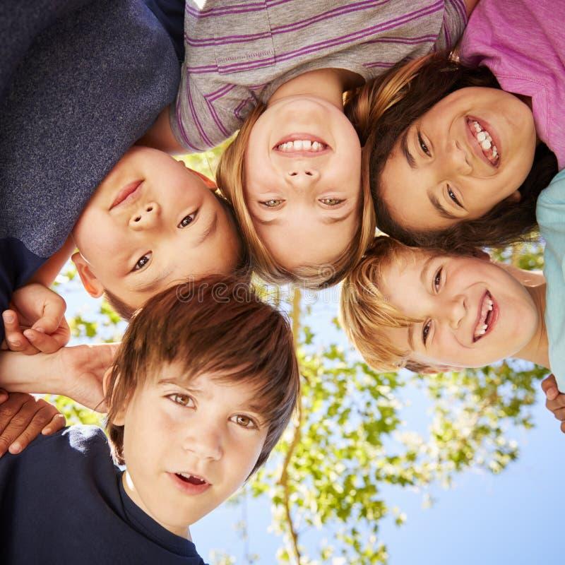 Vijf schoolkinderen die zich in een cirkel en het glimlachen bevinden royalty-vrije stock afbeeldingen