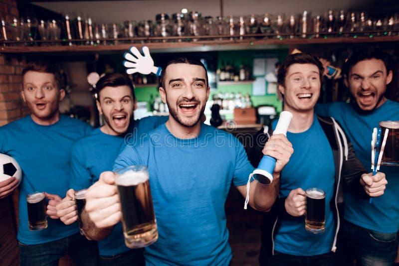 Vijf sportenventilators die bier drinken die en bij sportenbar vieren toejuichen royalty-vrije stock afbeelding