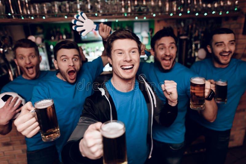 Vijf sportenventilators die bier drinken die en bij sportenbar vieren toejuichen stock afbeeldingen