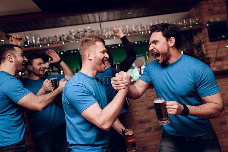 Vijf sportenventilators het drinken draagt toejuichend bij sportenbar Het schudden dient viering in royalty-vrije stock foto