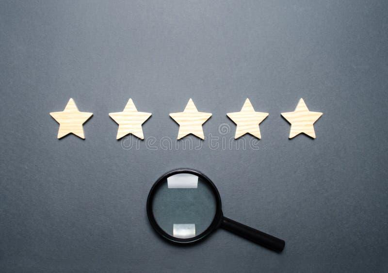Vijf sterren en een vergrootglas Classificatie van hotels en restaurants, dure instellingen Bekendheid en uniciteit, het aantrekk royalty-vrije stock afbeelding