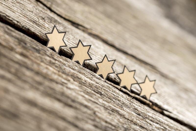 Vijf sterren op een rij op rustieke houten raad royalty-vrije stock afbeelding