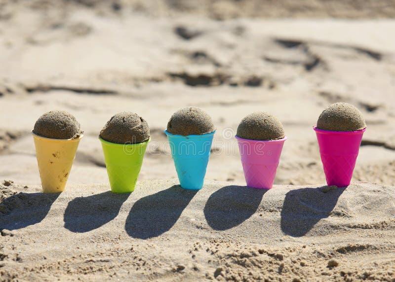 vijf stuk speelgoed roomijskegels op het overzeese strand met zand stock foto