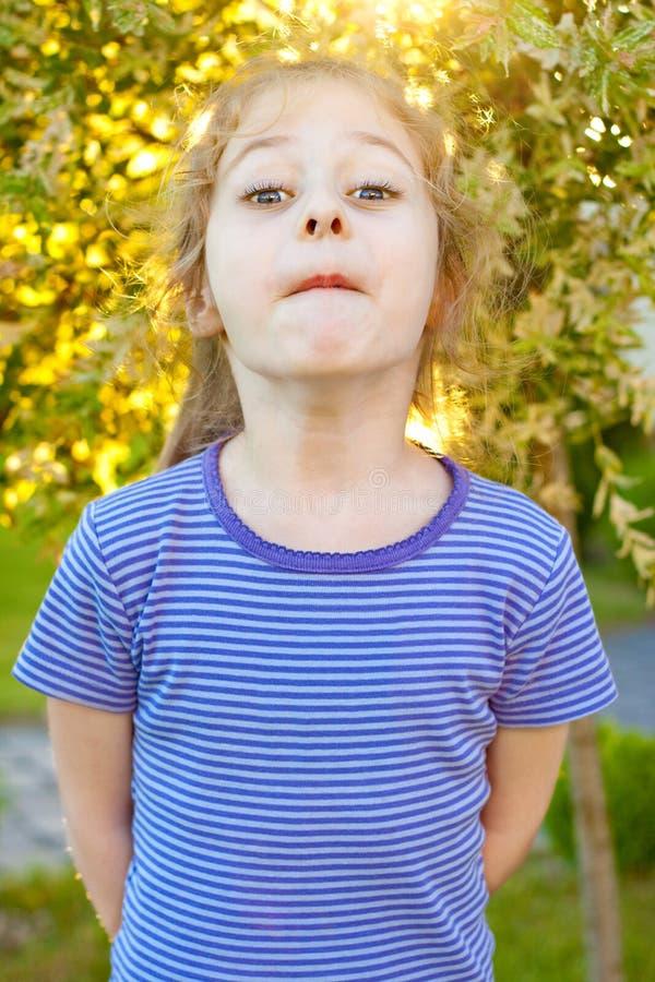 Vijf van het oude kindjaar meisje die gezichten in de tuin maken royalty-vrije stock fotografie