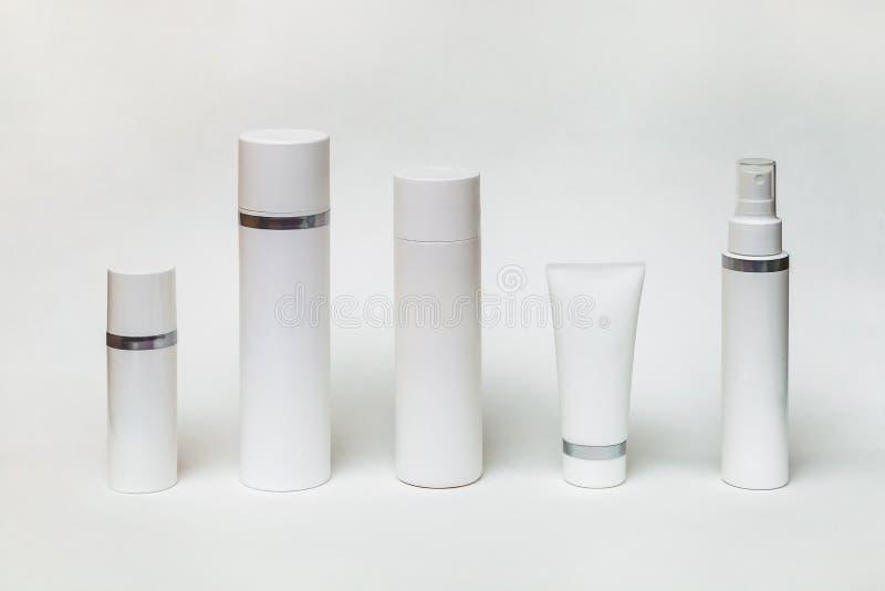 Vijf verschillende witte flessen en buizen voor schoonheidsmiddelen royalty-vrije stock afbeeldingen