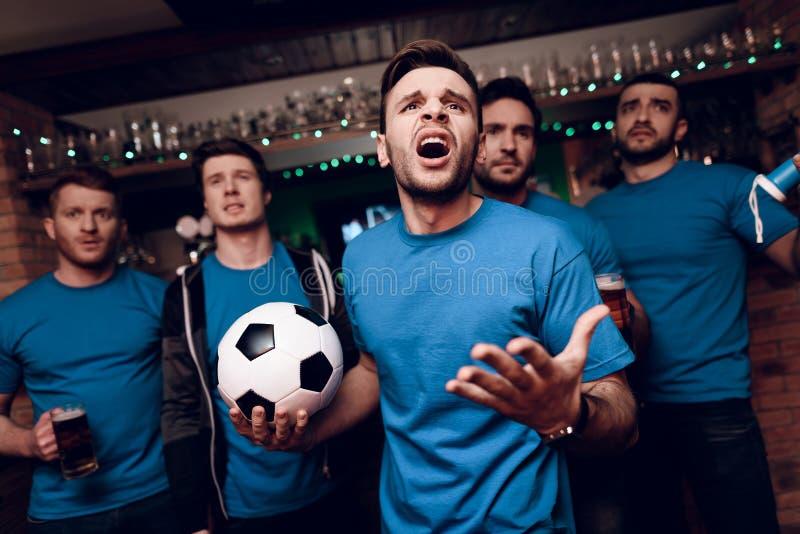 Vijf voetbalventilators die droevig bier drinken dat hun team bij sportenbar losmaakt royalty-vrije stock fotografie