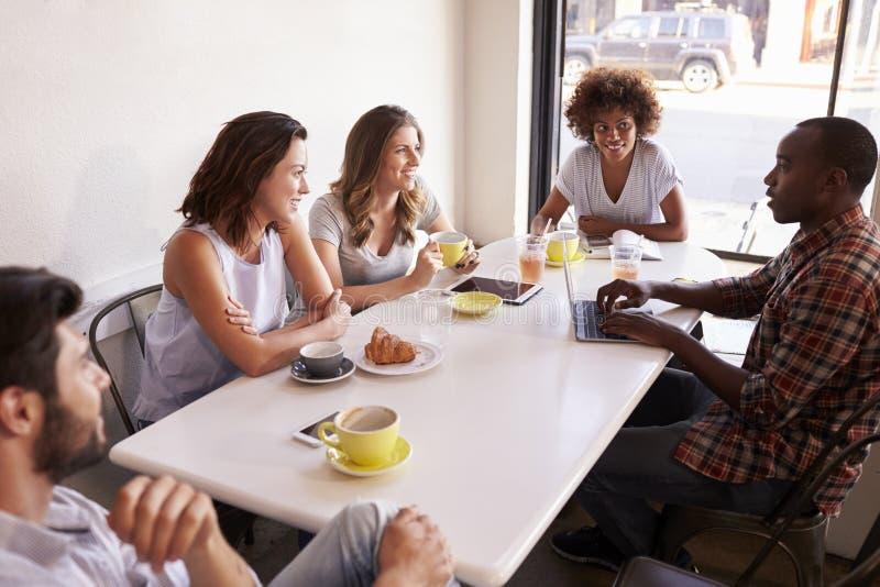 Vijf volwassen vrienden die in een koffie, opgeheven mening dicht omhoog zitten royalty-vrije stock foto