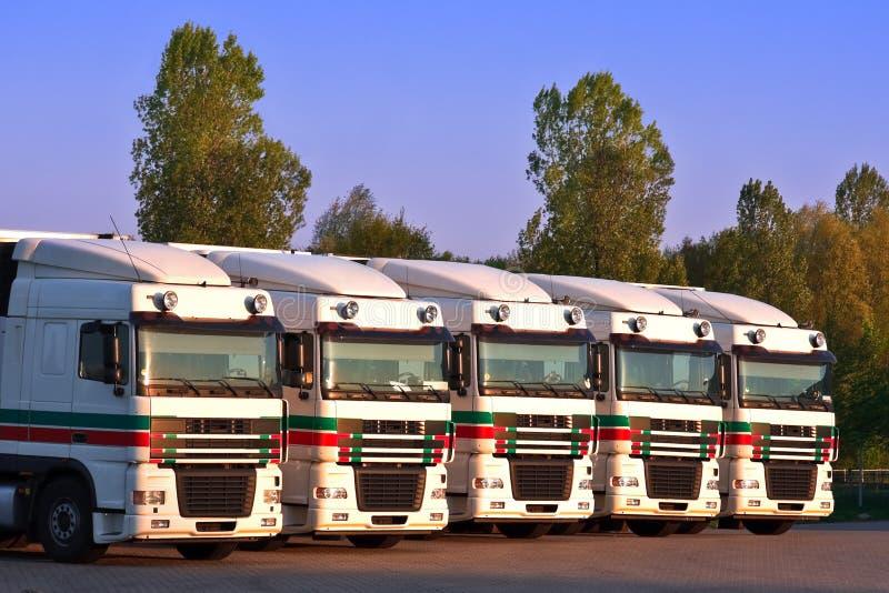 Vijf vrachtwagens in een rij met bomen en blauwe hemel stock foto's