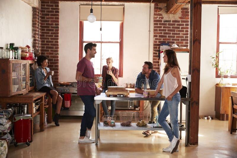 Vijf vrienden die uit over koffie in keuken volledige lengte
