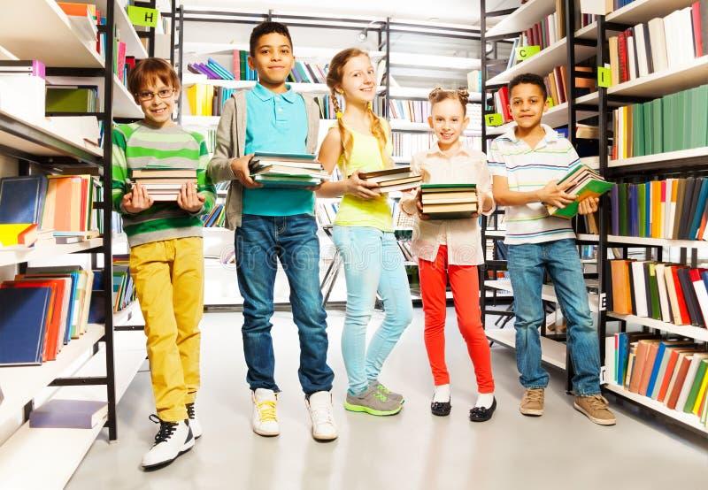 Vijf vrienden met stapels van boeken in bibliotheek stock foto's