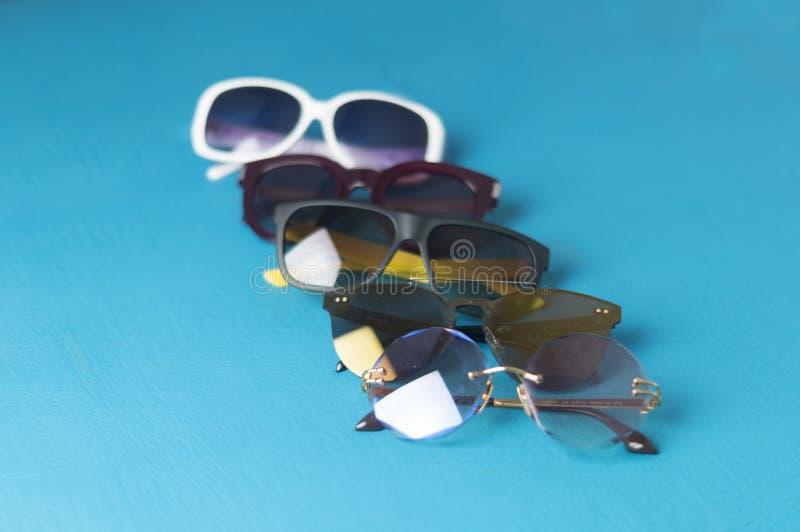 vijf zonnebril in verschillende ontwerpen en kleuren stock fotografie