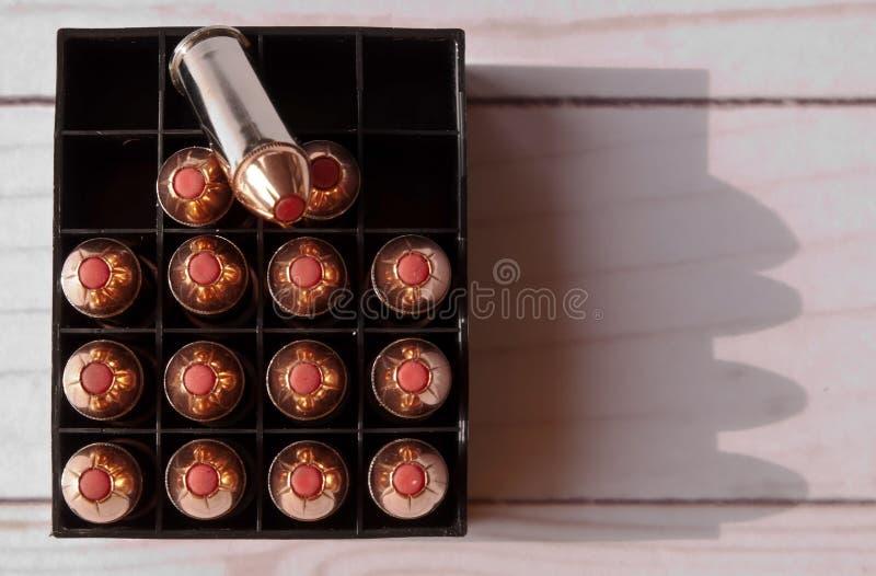 Vijftien 44 speciale kogels met rode uiteinden in een geval met één van de kogels op bovenkant stock foto's