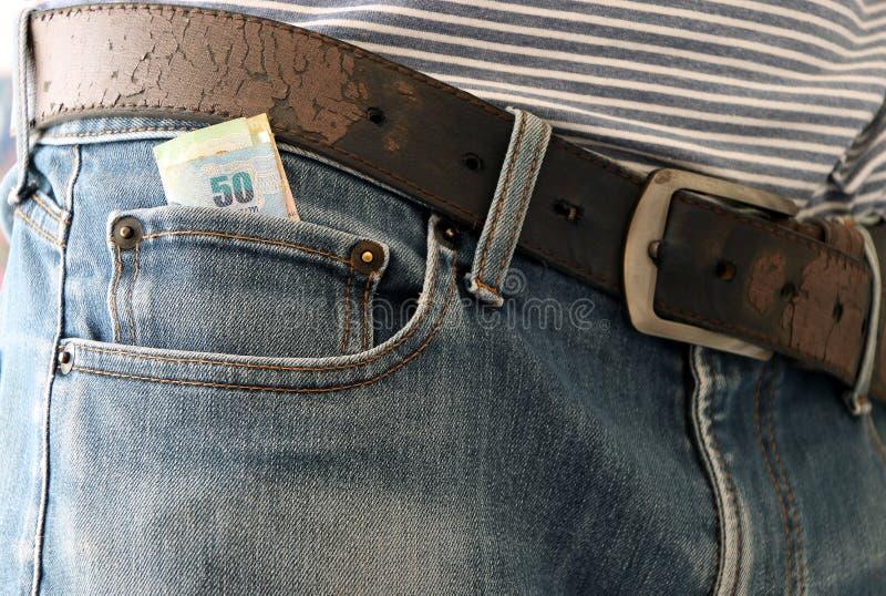 Vijftig Bahtbankbiljet van Thailand in de minizak van jeans met riem stock foto's