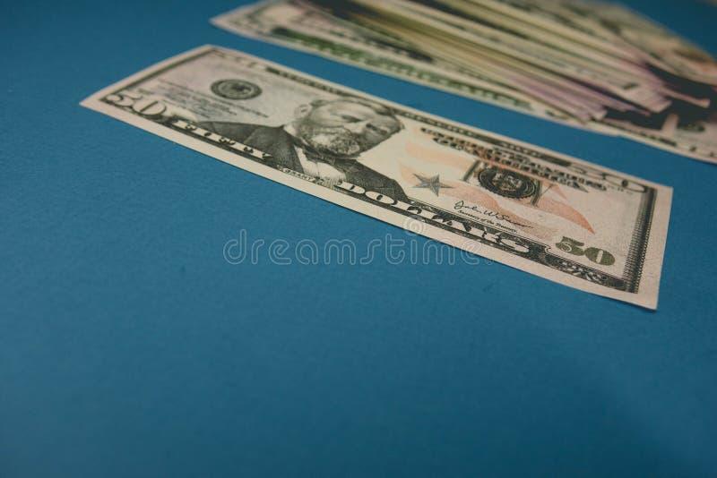 Vijftig dollarrekening op een blauwe achtergrond die door een vergrootglas worden bestudeerd royalty-vrije stock afbeelding
