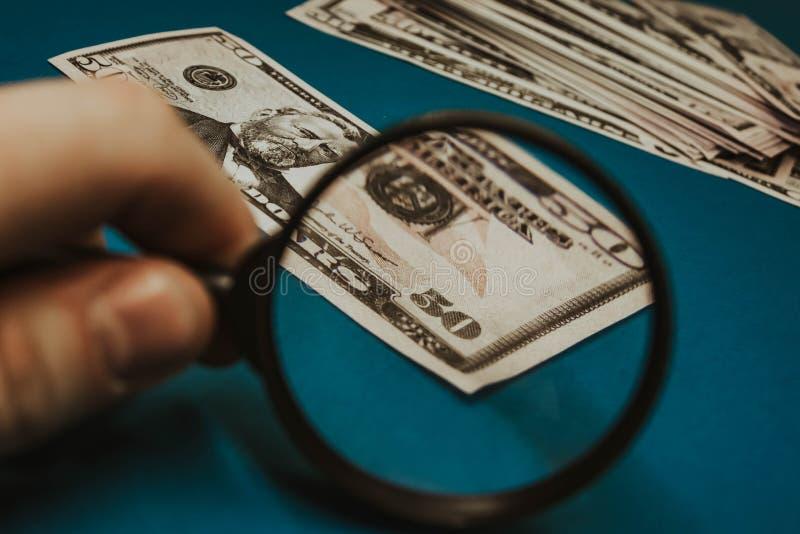 Vijftig dollarrekening op een blauwe achtergrond die door een vergrootglas worden bestudeerd royalty-vrije stock foto's