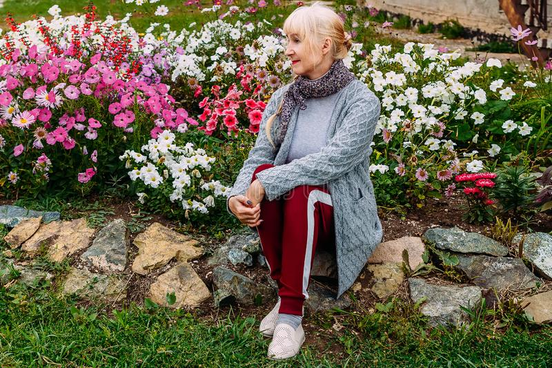 Vijftig-jaar-oude aantrekkelijke blondevrouw in een grijze cardiganzitting onder de bloeiende kleurrijke petunia royalty-vrije stock fotografie