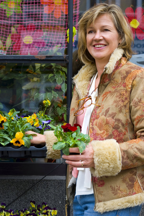 Vijftig vrouw het kopen bloemen stock afbeelding