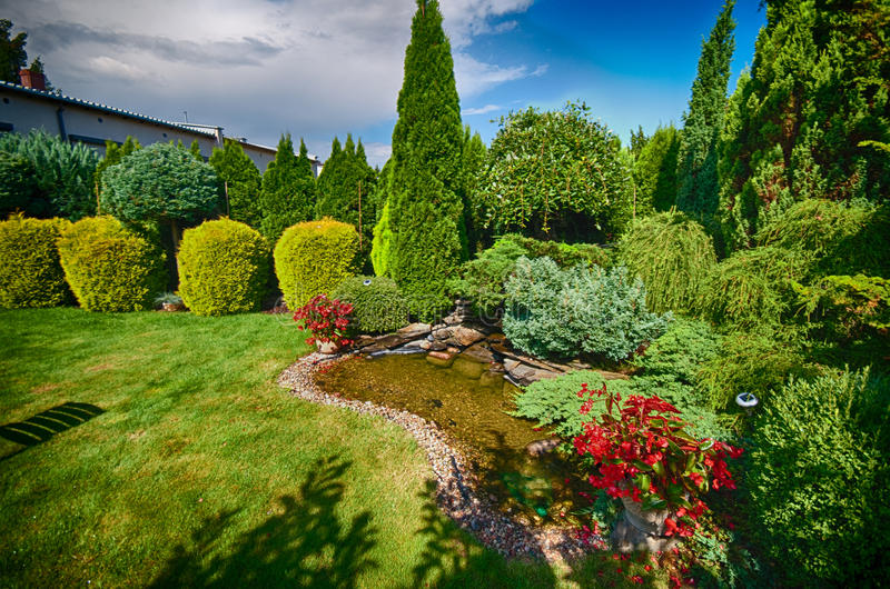 Vijver in gemodelleerde tuin stock foto