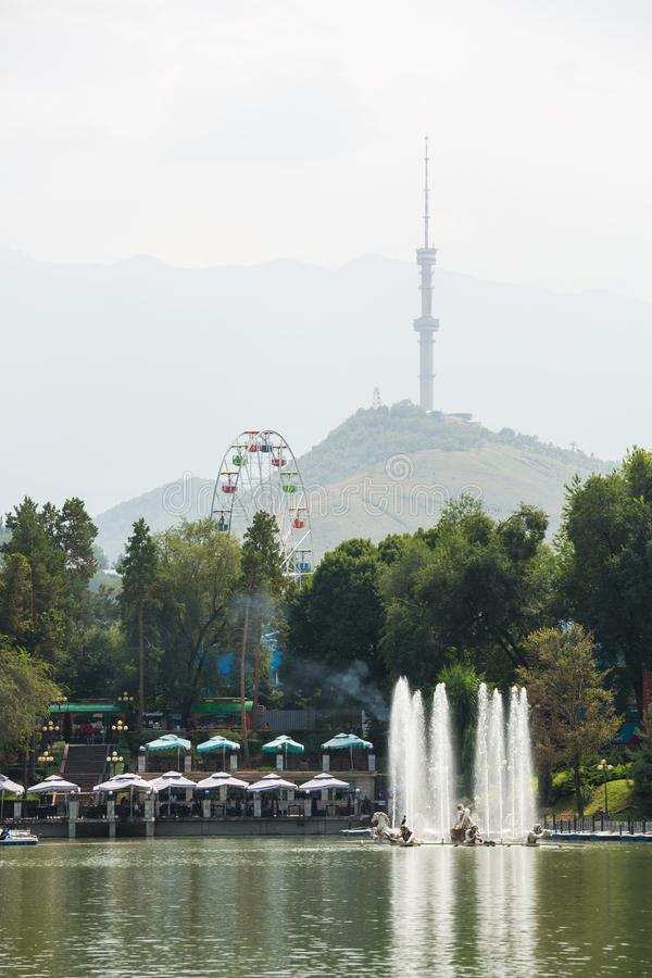 Vijver in het pretpark in de middag De toren en de bergen van TV van Alma Ata zijn op de achtergrond Alma Ata, Kazachstan royalty-vrije stock afbeelding