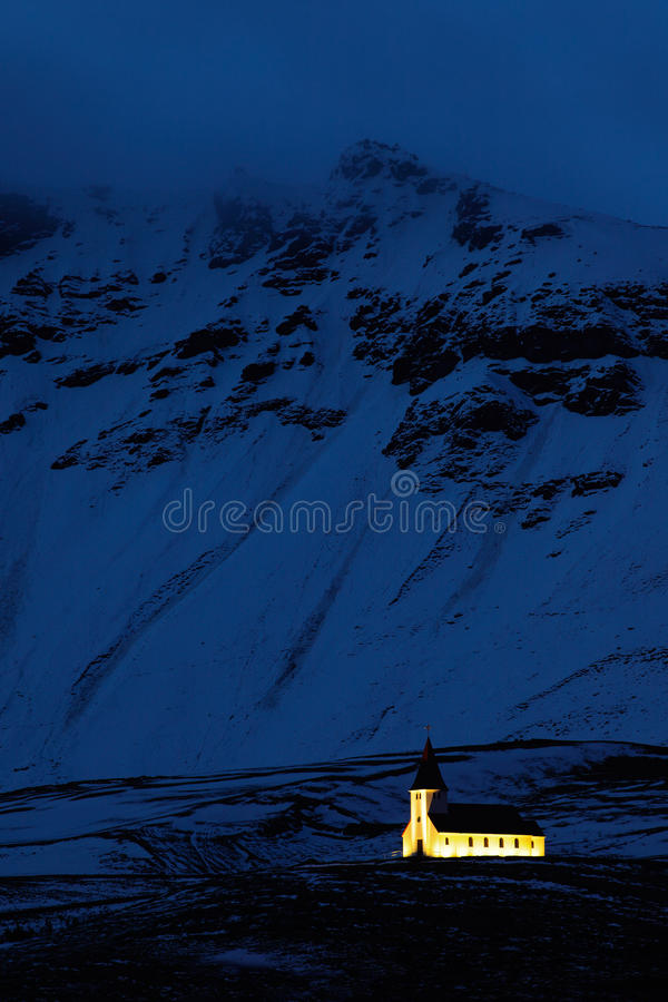 Vik教会在冰岛 与轻的教会和深蓝多雪的山的夜照片 从冷的冰岛的冬天场面 狂放的自然机智 免版税库存照片