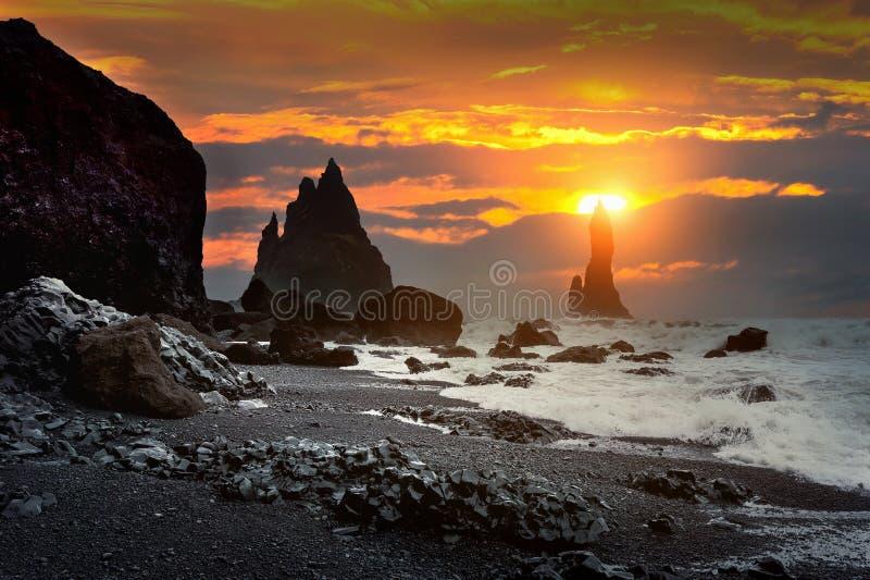 Vik und Basaltsäulen bei Sonnenuntergang, schwarzer Sand-Strand in Island stockfotografie