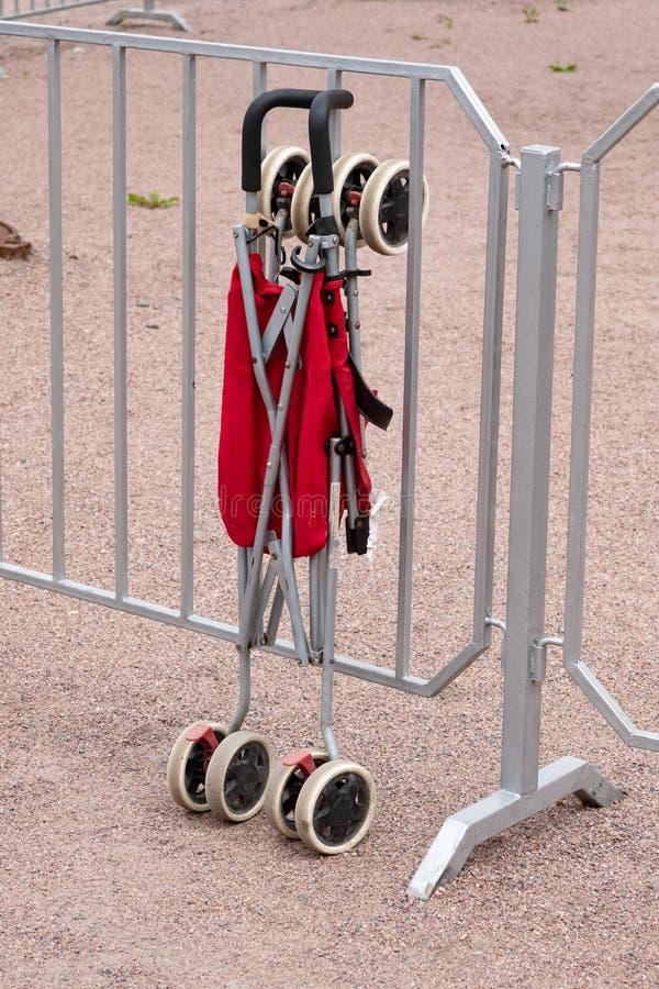 Vikande sittvagn för barn i rött som står på staketet arkivbild