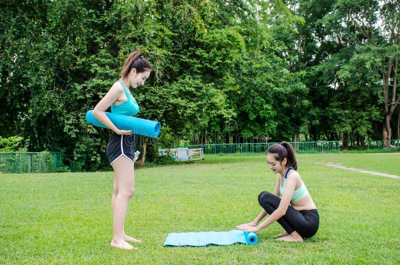 Viker härlig ung kvinna två yoga eller kondition som är matta för eller efter sportövning på gräset arkivfoton