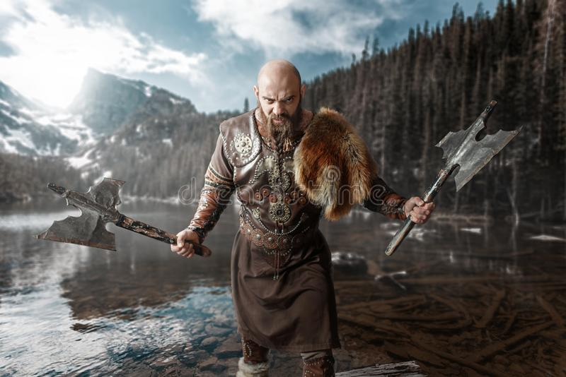 Viking with axes in hands standing at the lake. Viking with axes in hands dressed in traditional nordic clothes standing at the lake. Ancient warrior at the stock images