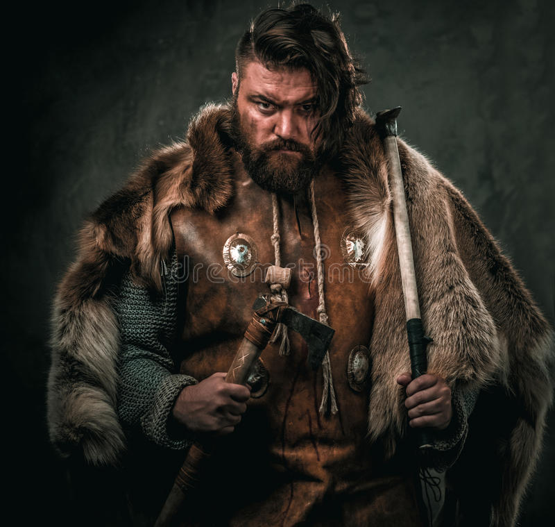 Viking with cold weapon in a traditional warrior clothes royalty free stock photography