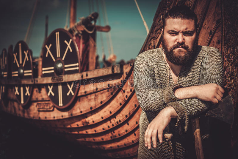 Viking con el hacha que se coloca cerca de drakkar en la costa fotografía de archivo libre de regalías
