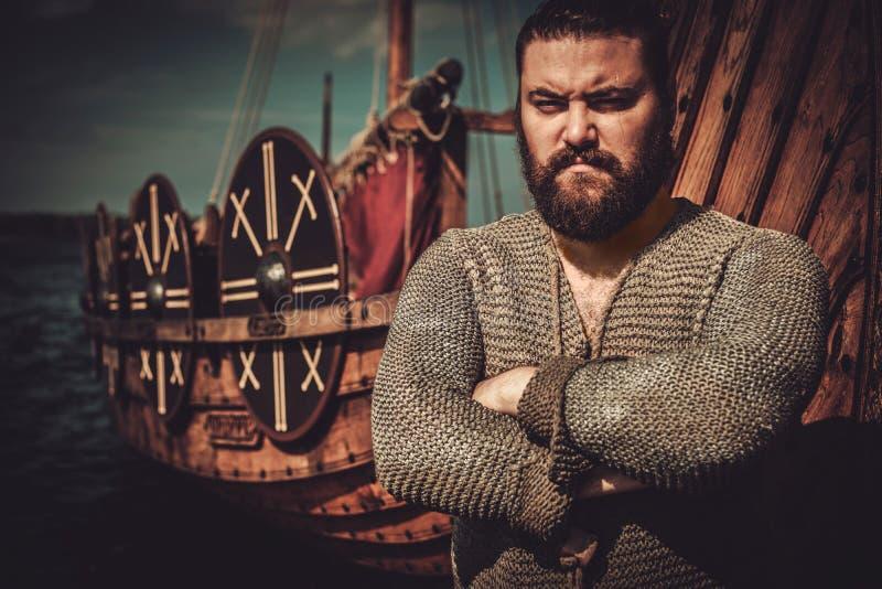 Viking con el hacha que se coloca cerca de drakkar en la costa imagenes de archivo