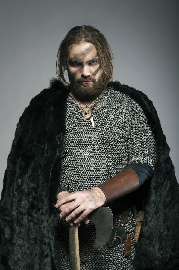 Viking en la situación de la piel se inclina en su hacha en el fondo gris fotografía de archivo