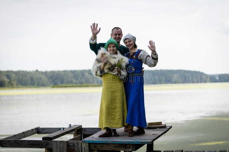 Viking family on a pier on a lake. a man, woman, and teenage girl wave their hands in greeting. Reconstruction of the historical costume and life of the early royalty free stock photos