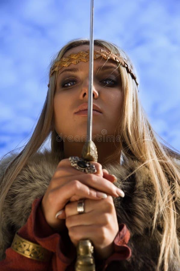Viking girl warrior on a blue sky background stock photos