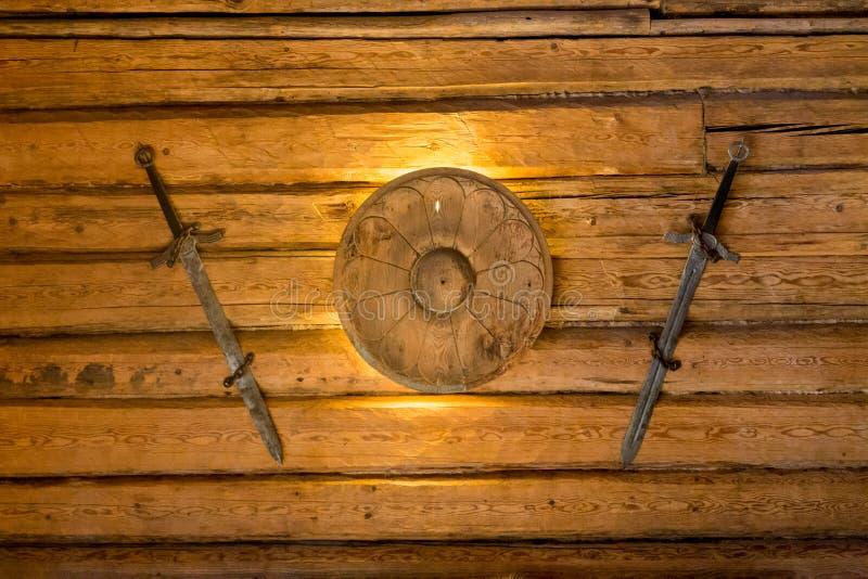 Viking-Klingen und kleines Schild, die an der hölzernen Wand hängen stockfoto